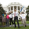 President Barack Obama uses a light saber as he watches a demonstration of fencing at an event supporting Chicago's 2016 host city Olympic bid, on the South Lawn of the White House in Washington. At rear is Chicago Mayor Richard Daley and first lady Michelle Obama.